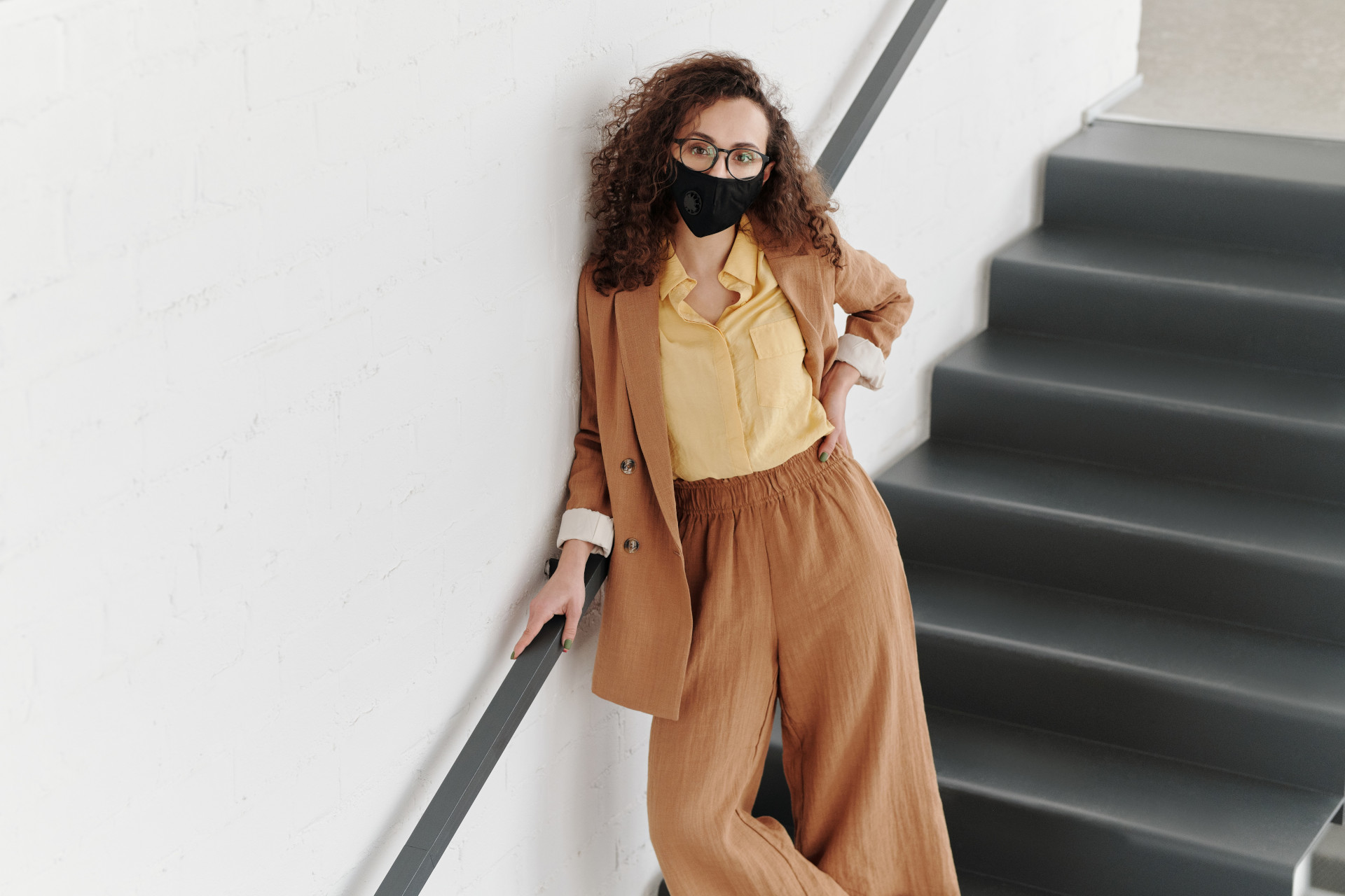 woman-with-a-face-mask-standing-on-stairs-4347460